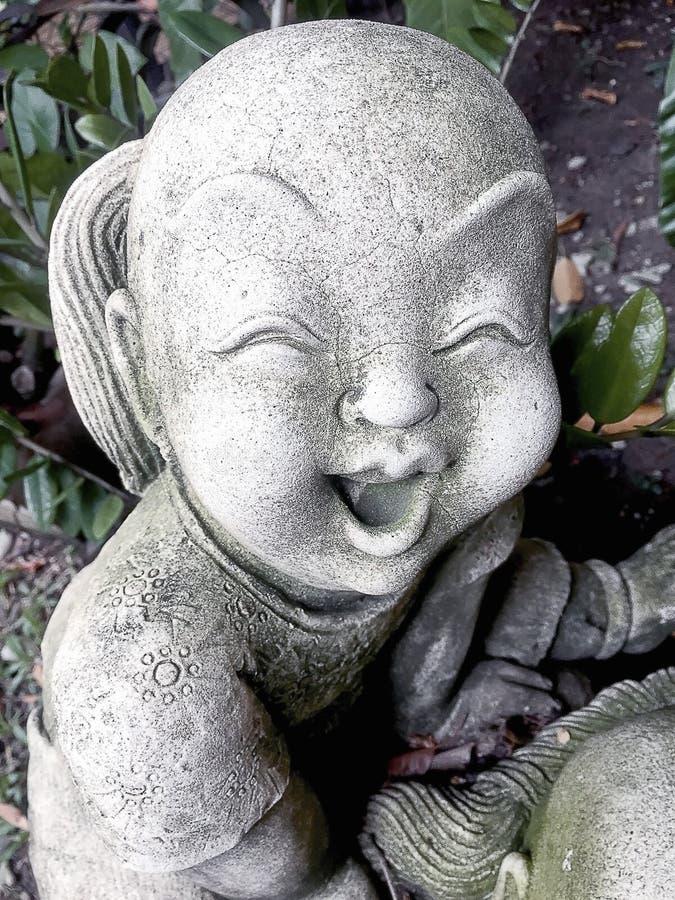 Staty av en gammal le pojke arkivbilder