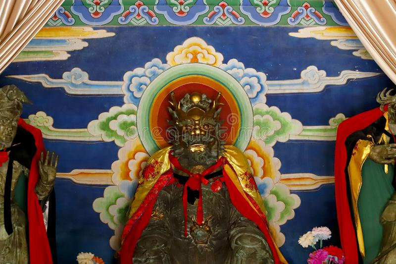 Staty av en gud i en tempel i de kinesiska trädgårdarna av den svarta Dragon Pool i Jade Spring Park, Lijiang, Yunnan, Kina royaltyfria bilder