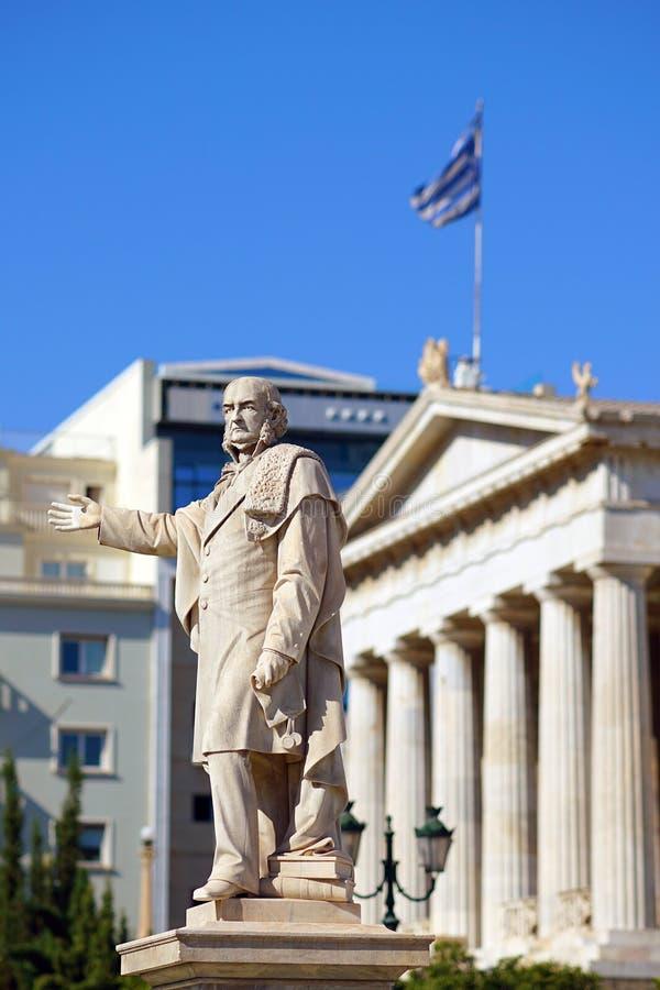Staty av en man framme av universitetet av Aten arkivfoton