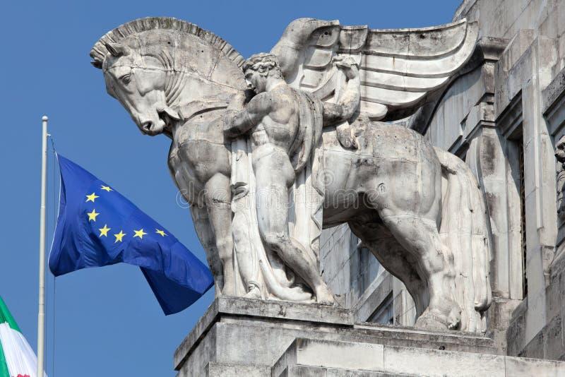 Staty av en man som rymmer en bevingad häst på Milan huvudsakliga järnvägsstation royaltyfri foto