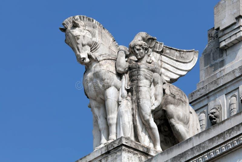 Staty av en man som rymmer en bevingad häst på Milan huvudsakliga järnvägsstation arkivbild