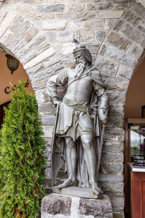 Staty av en riddare på ingången till det kungligt för stång som lokaliseras nära den Pelesh slotten i Sinaia, i Rumänien fotografering för bildbyråer