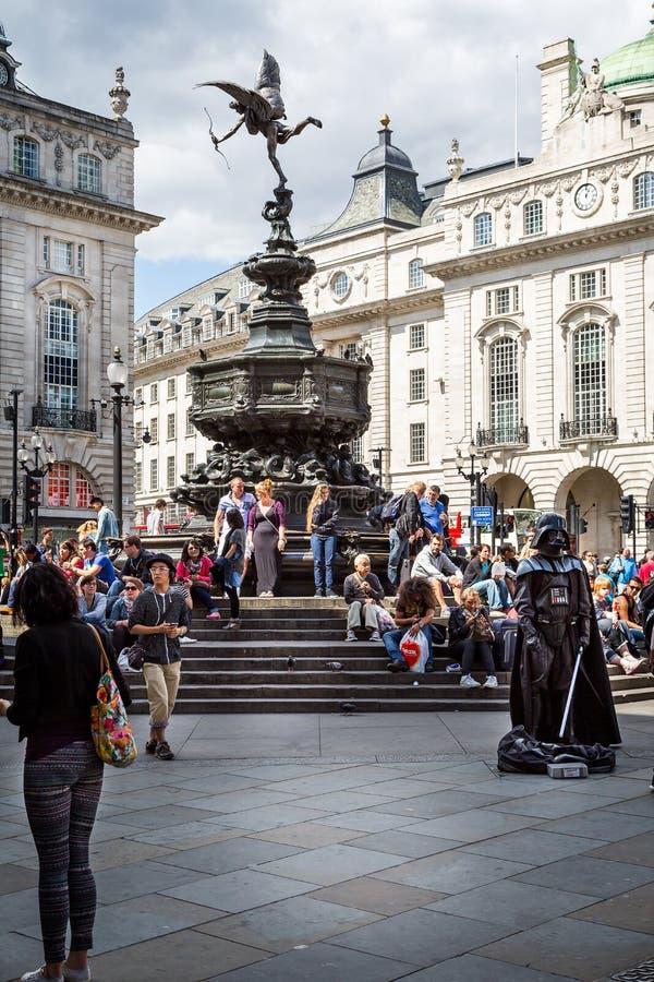 Staty av Eros eller Anteros med den Darth Vader gataaktören i den Picadilly cirkusen, London, UK royaltyfri foto