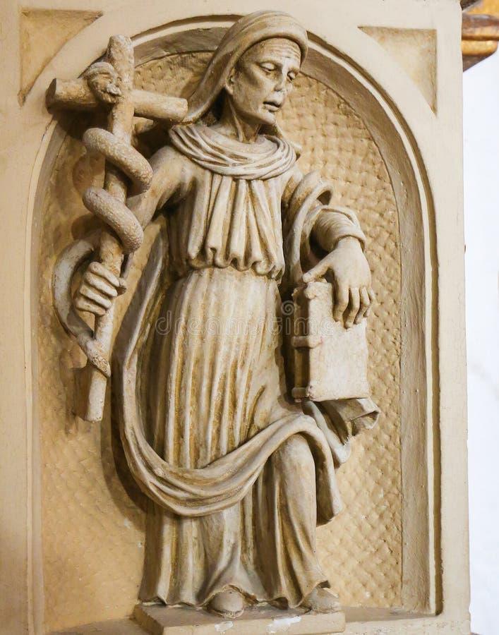 Staty av ett helgon som rymmer ett kors med en orm i cathedraen arkivfoto