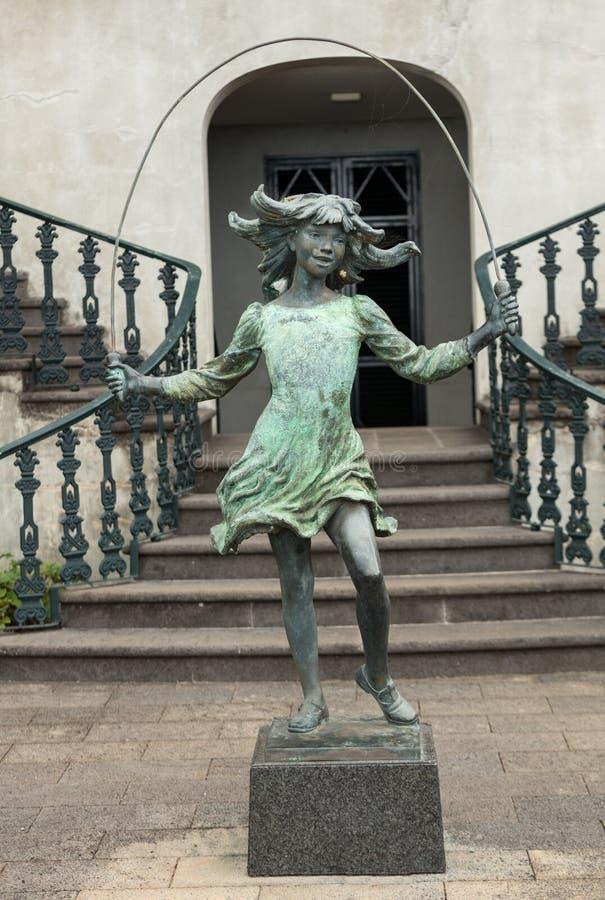Staty av flickan med hoppa over-repet i botaniska trädgården Monte av Funchal, royaltyfri bild