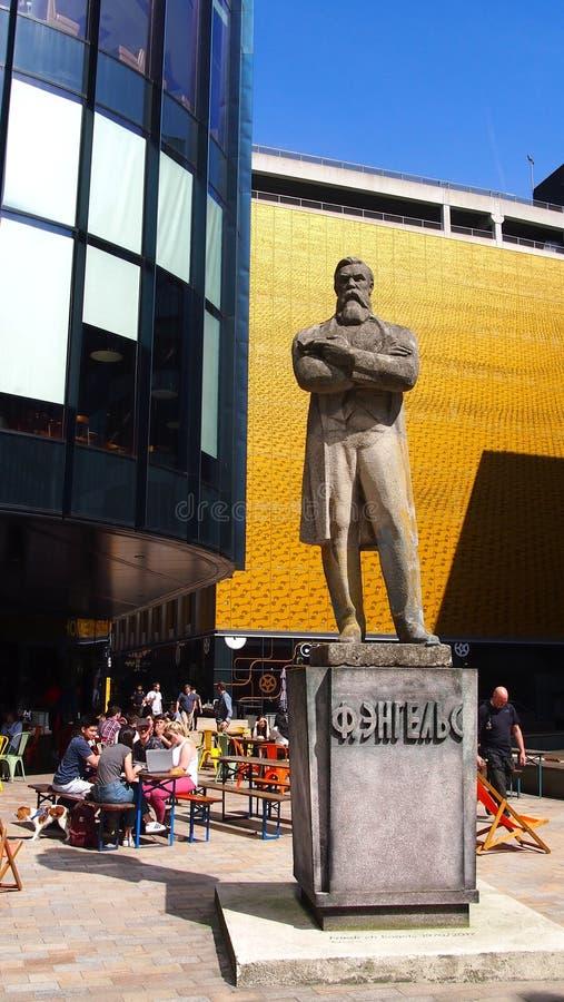 Staty av Friedrich Engels utanför den hem- kulturella mitten i Manchester, England arkivbilder