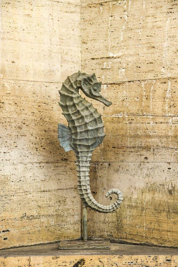 Staty av havshästen på bakgrundsstenväggen av tuffspringbrunnen arkivbild