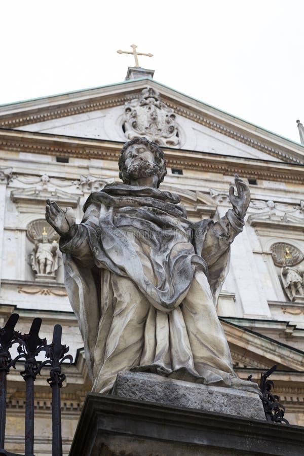 Staty av helgonet på bakgrunden av en medeltida kyrka med ett kors royaltyfria bilder