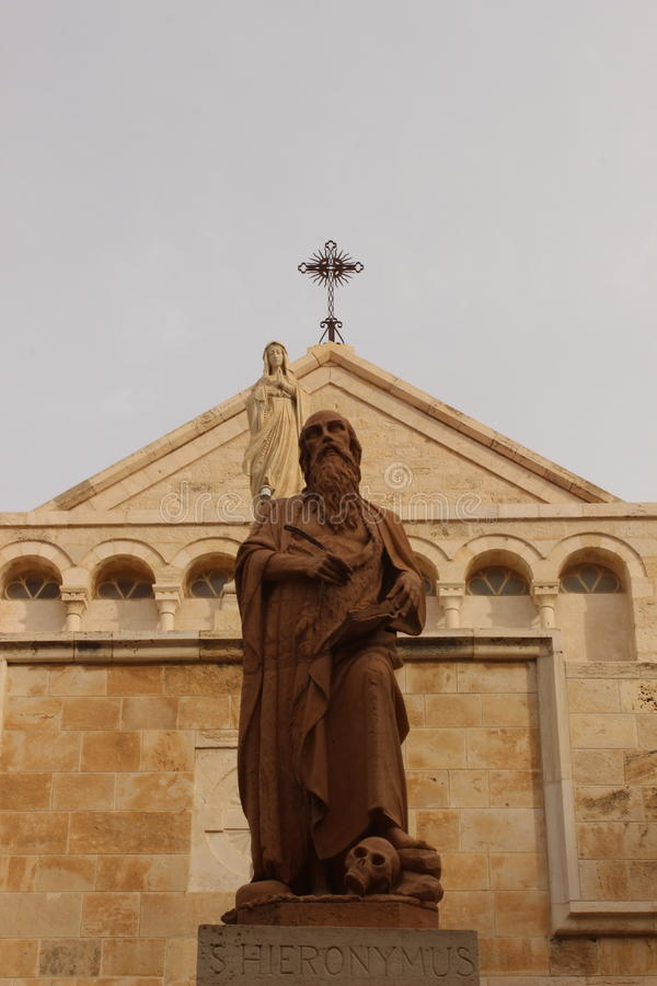 Staty av Hieronymus framme av Kristi födelsekyrkan i Betlehem arkivfoto