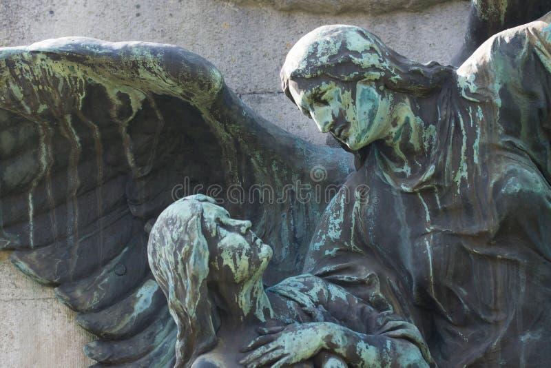Staty av himmelskt vara ängel som vägleder en människa arkivbild