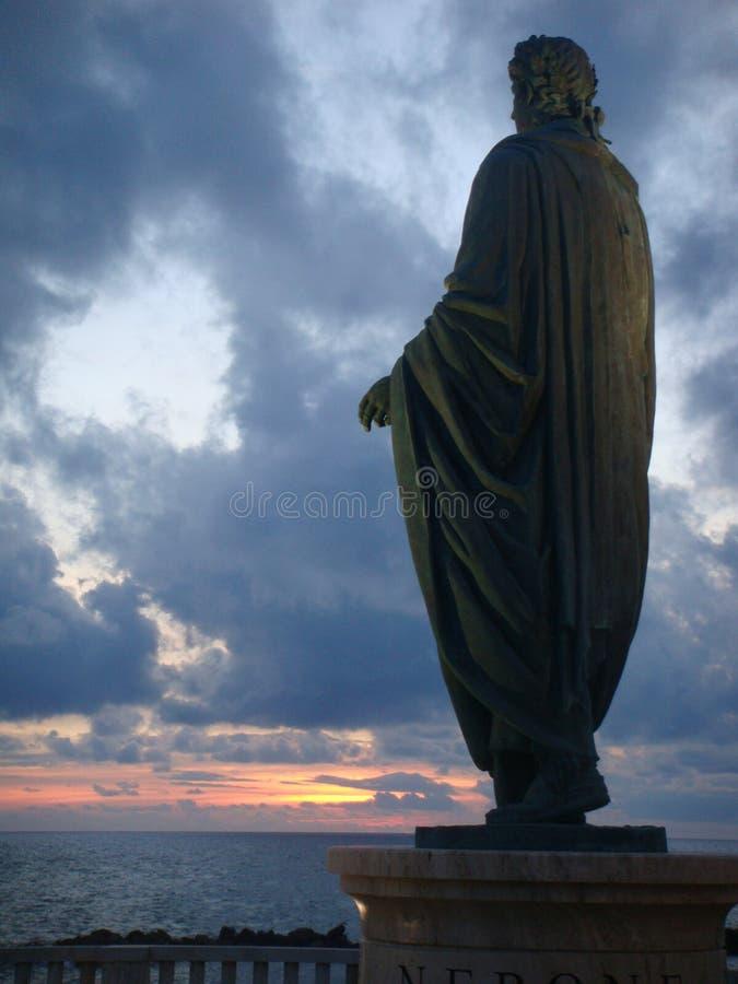 Staty av kejsaren Nero som bakifrån ses med havet till solnedgången till Anzio i Italien fotografering för bildbyråer