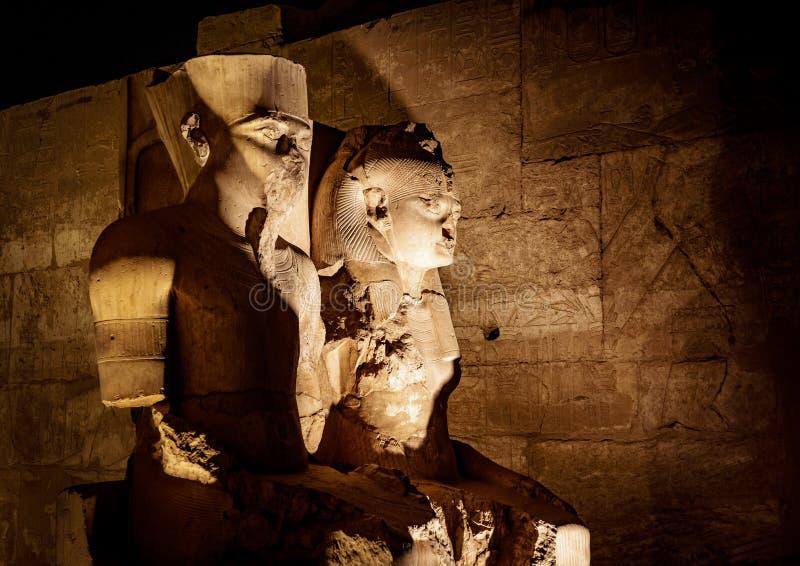 Staty av konungen Tutankhamun och hans drottning på templet av Luxor i den Luxor staden Thebes i Egypten, exponerad på natten royaltyfri fotografi
