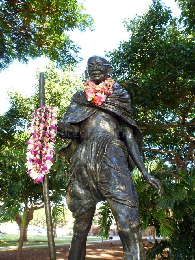 Staty av Mahatma Gandhi som rymmer en gå pinne och bär rea royaltyfri fotografi