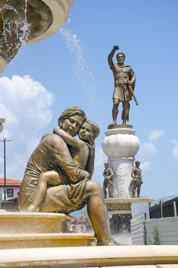 Staty av modern & son och staty av Alexander det stort i bakgrund, i mitt av Skopje arkivfoto