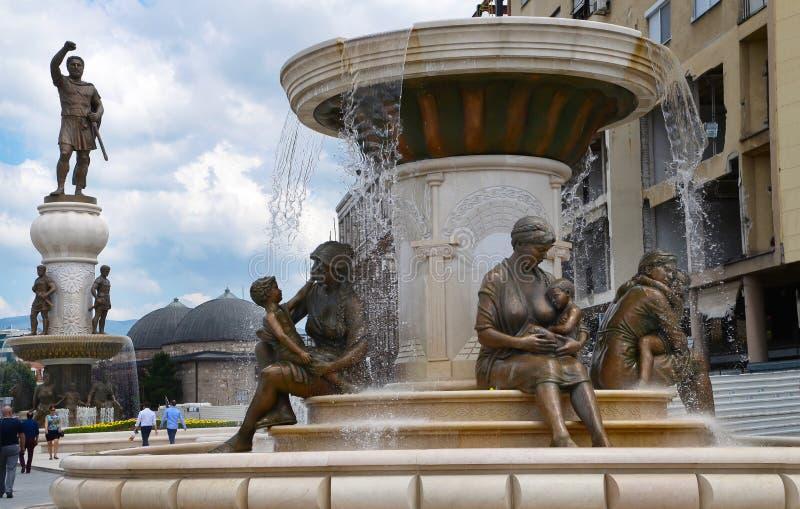 Staty av modern & son och staty av Alexander det stort i bakgrund, i mitt av Skopje (centrum), Makedonien ( royaltyfri foto
