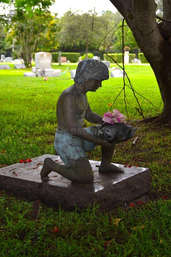 Staty av pojken som knäfaller på allvarlig plats royaltyfria foton