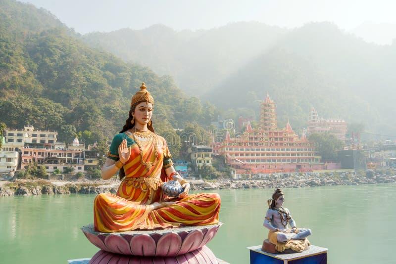 Staty av sammanträdegudinnan Parvati och staty Shiva på flodstranden av Ganga i Rishikesh arkivbilder
