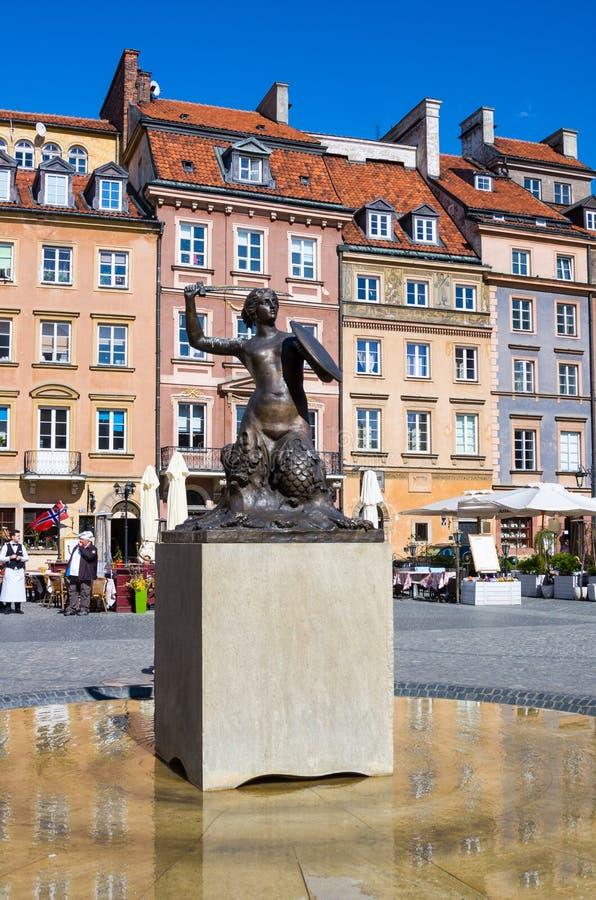 Staty av sjöjungfrun Syrenka - symbol av Warszawa på den gamla stadmarknadsfyrkanten mot hyreshusar och beträffande arkivbild