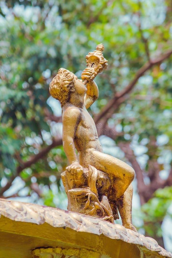Staty för guld- pojke på springbrunnen fotografering för bildbyråer