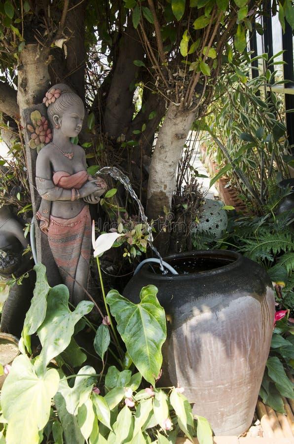 Staty för leradockakvinna av att arbeta i trädgården garnering i trädgård royaltyfria bilder
