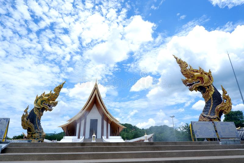 Staty för två Naga, konung av nagasormdjuret i buddistisk legend och moln för blå himmel i bakgrund på dhammayan wat, Thailand arkivbild