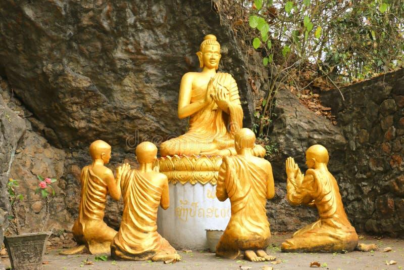 Staty guld- sittande buddha som omges av munken, Phou sikulle, Lua royaltyfri bild