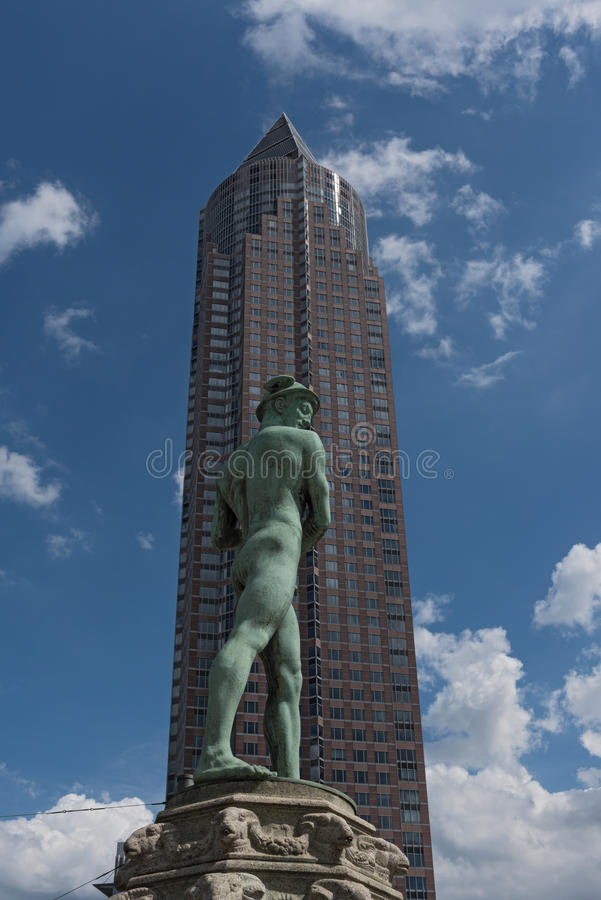 Staty i Friedrich Ebert Anlage framme av Messeturmen i Frankfurt, Tyskland arkivbild