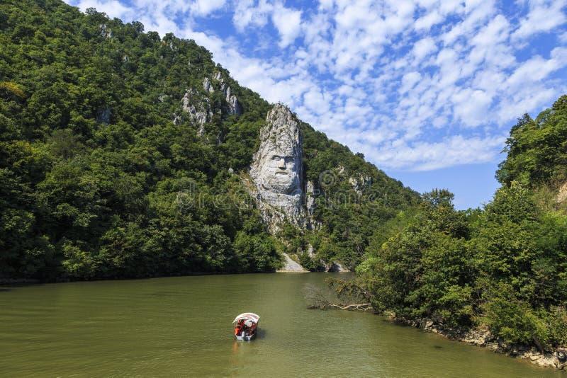 Staty som snidas i sten över floden arkivfoto