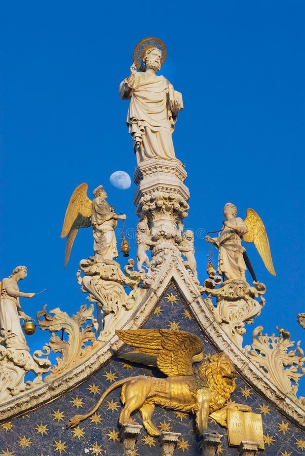 Statyer av lejonet, änglar och Jesus Christ som dekorerar övrefasaden av Stets Mark basilika i Venedig, Italien arkivbilder
