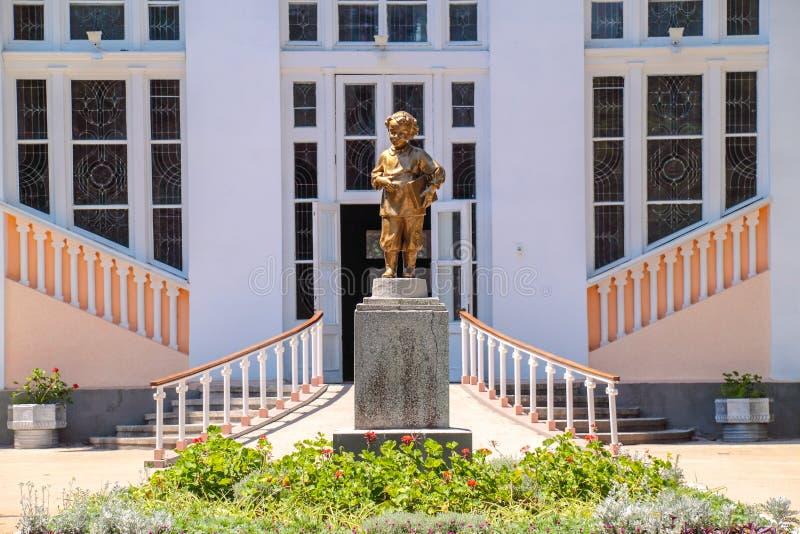 Statyer av pojken målade guld framme av den gamla USSR-stil logen arkivbild