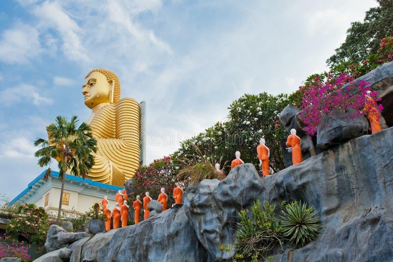 Statyer för buddistisk munk som går till den guld- Buddhatemplet, Dambulla, Sri arkivfoton