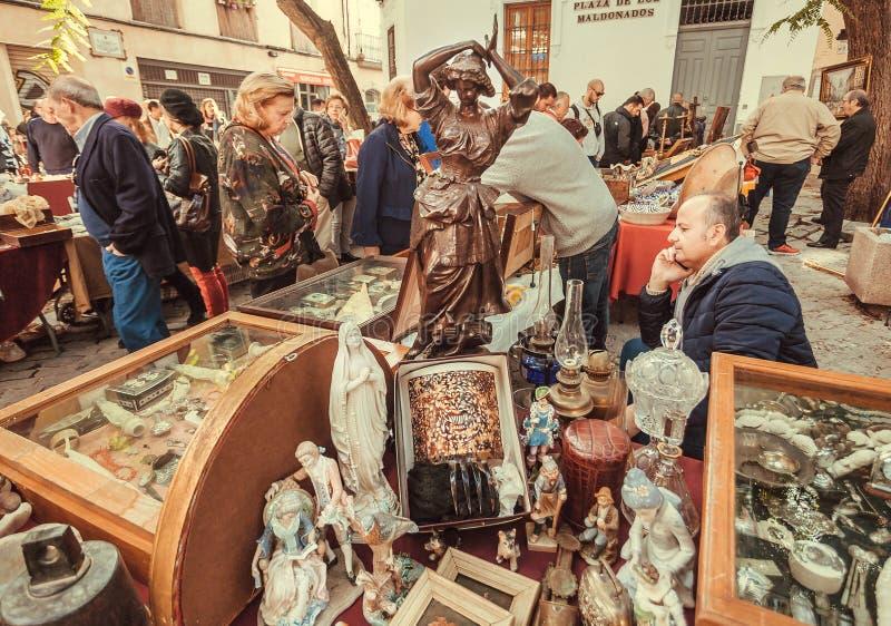 Statyer och annat tappningmaterial, gammal leksaker som är till salu på loppmarknaden med köpare, fynd, antikt möblemang royaltyfria foton