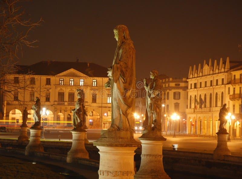 Statyer och byggnader på natten fotografering för bildbyråer
