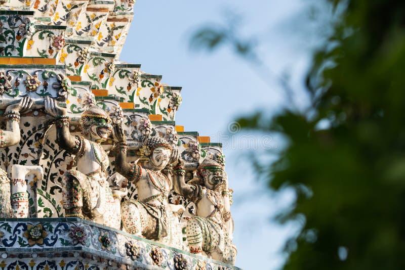 Statyer på fasaden av det Wat Arun tempeltaket på en solig dag i Bangkok, Thailand royaltyfri foto