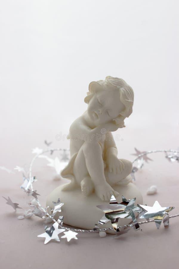 Statyett av en sova ängel på en vit bakgrund arkivfoton