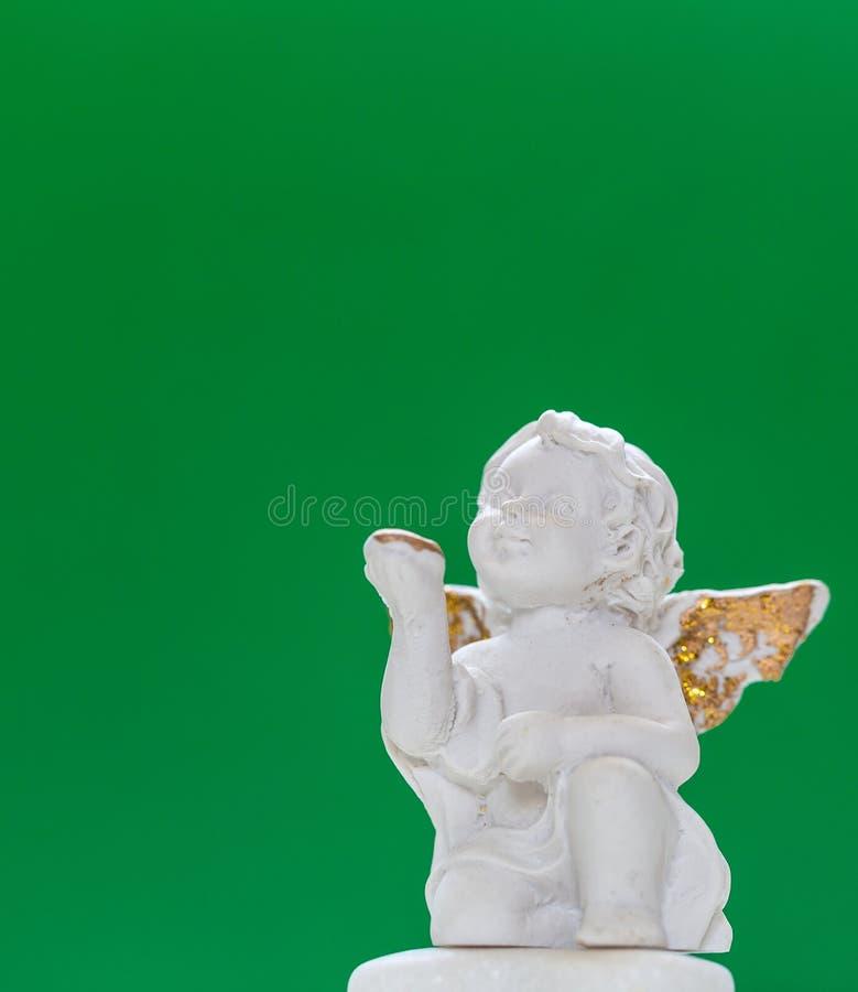 Statyetten av behandla som ett barn Angel On Green Background arkivbilder