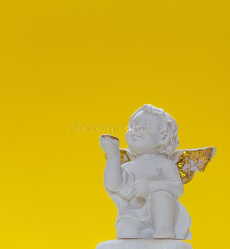 Statyetten av behandla som ett barn Angel On Yellow Background 1 royaltyfria bilder