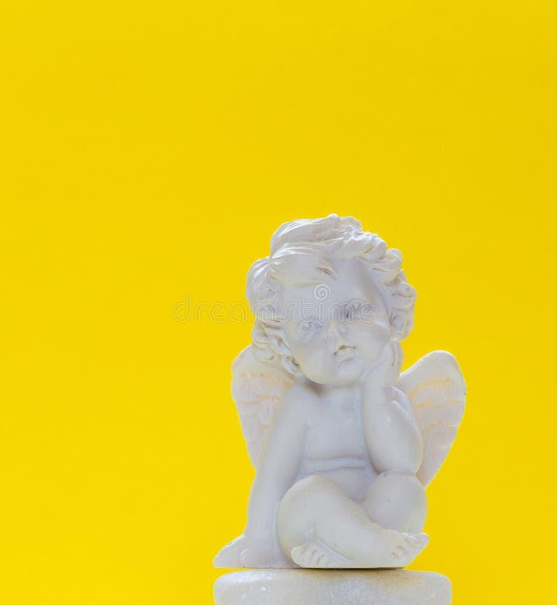 Statyetten av behandla som ett barn Angel On Yellow Background 1 royaltyfria foton