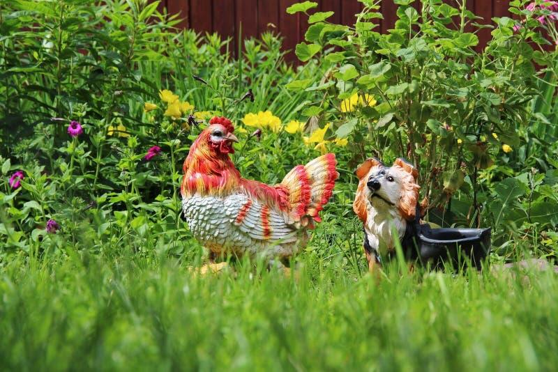 Statyetter höna och hund för garneringrabattträdgård fotografering för bildbyråer