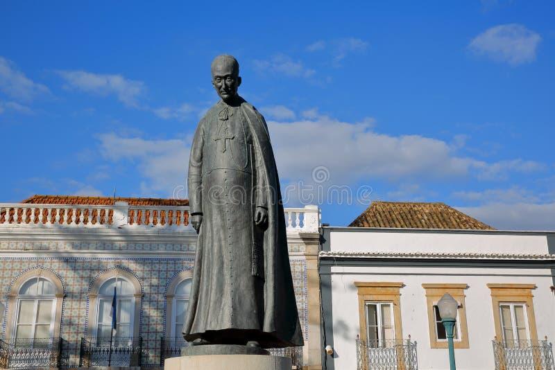 """Statyn av den Dom Marcelino Franco biskopen, †1871 """"1955, lokaliserat på Antonio Padinha Square, med historiska byggnader i bak royaltyfria foton"""
