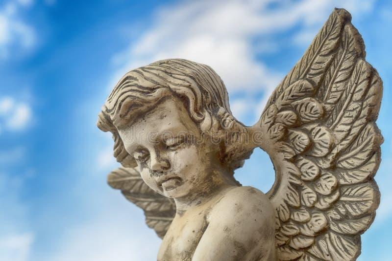 Statyn av en grå färg stenar ängel mot blå himmel arkivfoton
