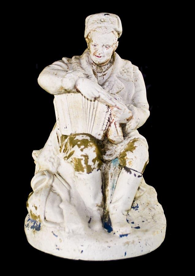 Statyn av en soldat med ett gammalt dragspel på en svart bakgrund arkivfoto
