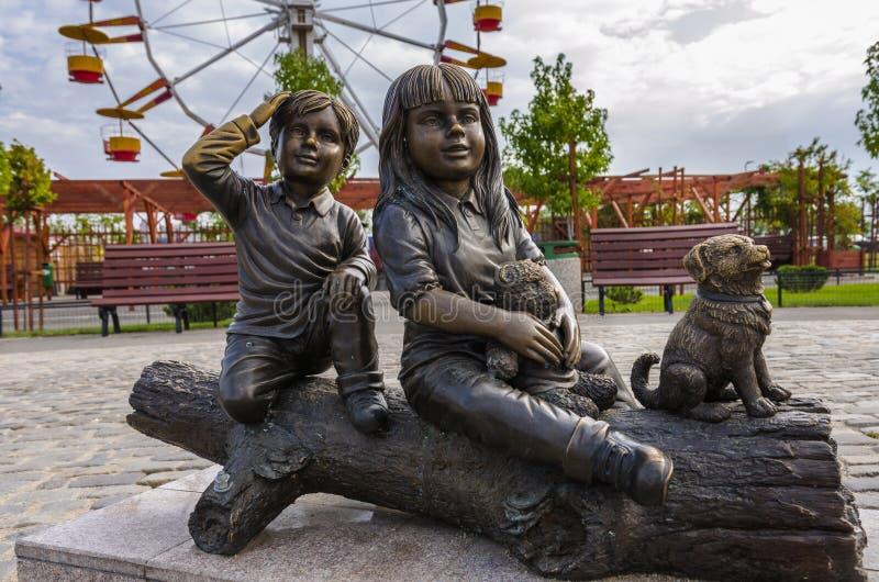 Statyn av två barn near liten vovve arkivbilder