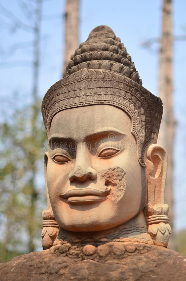 Statyn för den Angkor wattstenen av en khmervälden och det delikat fördärvar av Angkor arkivfoto
