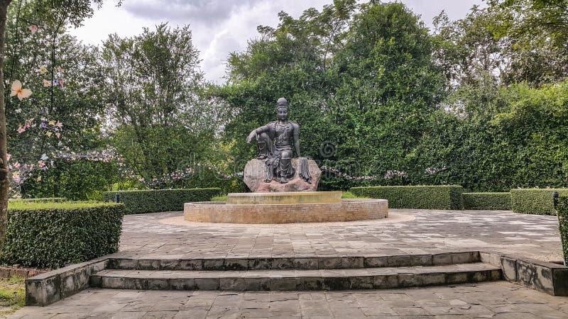 Statyn för den Avalokitesvara BodhisattvaBuddha är i trädgården som är ett behagfullt royaltyfria bilder