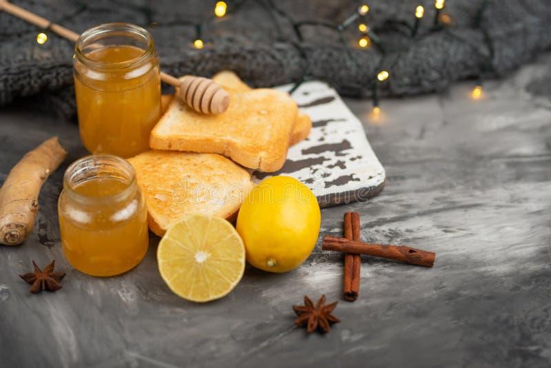 Stau mit Zitrone und Ingwer mit Toast und Gewürzen auf einem dunklen Hintergrund, mit Raum für eine Aufschrift Das Konzept der Hi lizenzfreies stockbild