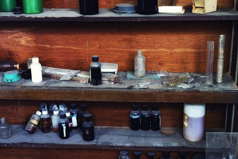 Staubige chemische Flasche auf Holzregal stockfoto