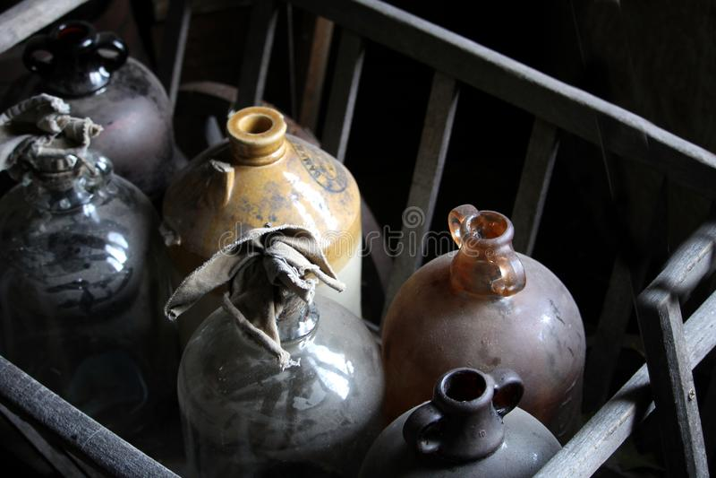 Staubige, rustikale alte Glaskorbflaschen oder Weinflaschen in einem hölzernen Ra lizenzfreies stockfoto