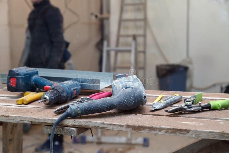 Staubiges Bohrgerät des Nahaufnahmeberufsbaus, Puncher auf Hintergrund des Arbeiters, Gebäudewerkzeuge Konzeptinstallation und stockbild