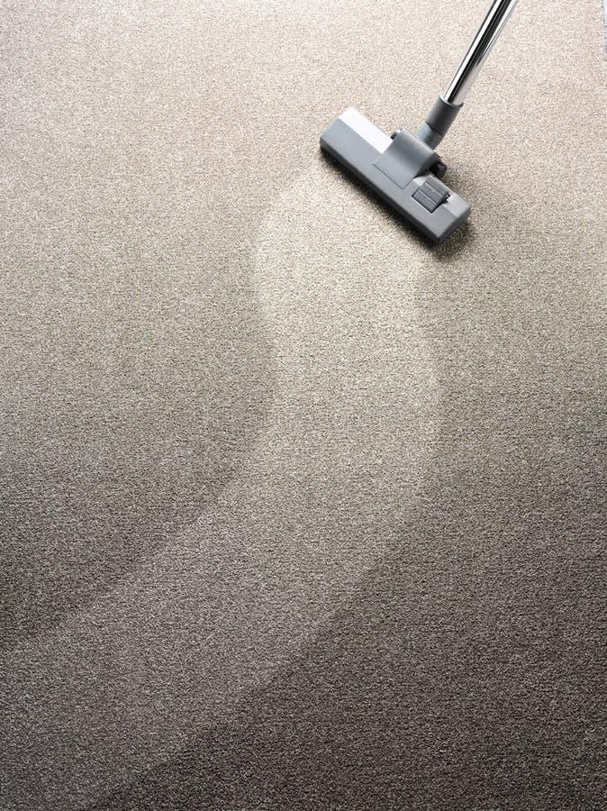Staubsauger auf einem Teppich mit einem sauberen Streifen für Kopienraum stockfotografie